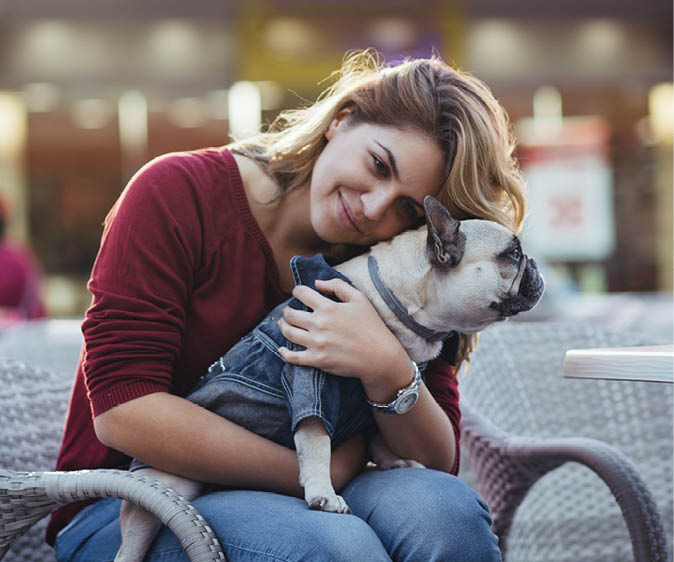 Woman with bulldog wearing accessories